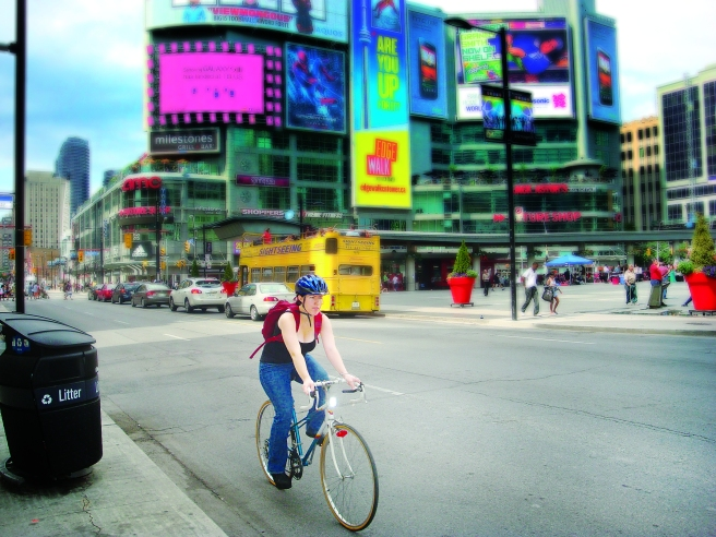 A woman wearing a helmet cycles near Yonge-Dundas Square in Toronto. A report in The Globe and Mail in February revealed that more than 1,200 cyclists are injured in Toronto annually.
