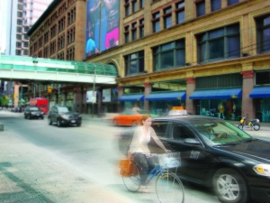 A woman cycles near the Eaton Centre along Queen Street West in Toronto. Collisions while riding can have long-term effects, including reduction of memory and concentration, impairment of motor skills, personality changes, severe depression, loss of speech and other language abilities, and paralysis.