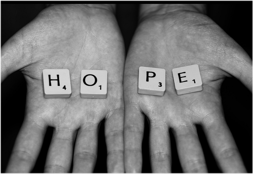 Hands holding Scrabble letters reading 'HOPE'