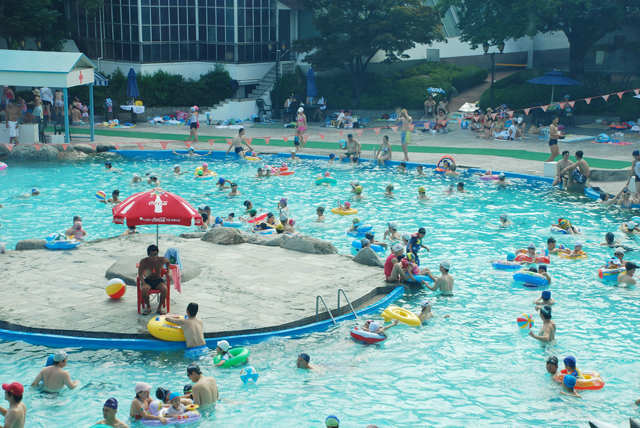 people swimming in an outdoor pool
