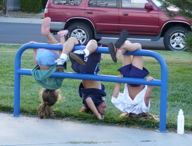 children hanging upside from fence