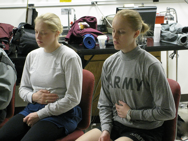 2 army women doing deep breathing exercises