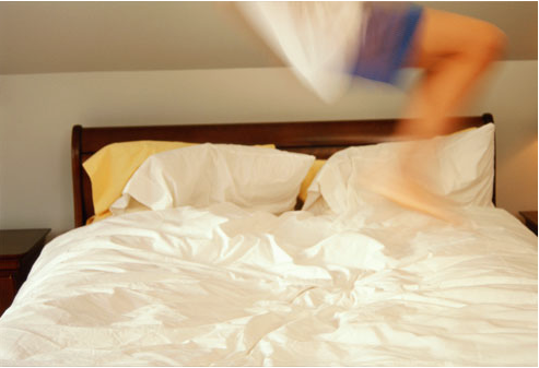 blurry image of kid jumping on bed
