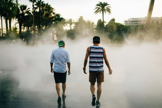 two men walking by a beach on the board walk on a foggy day
