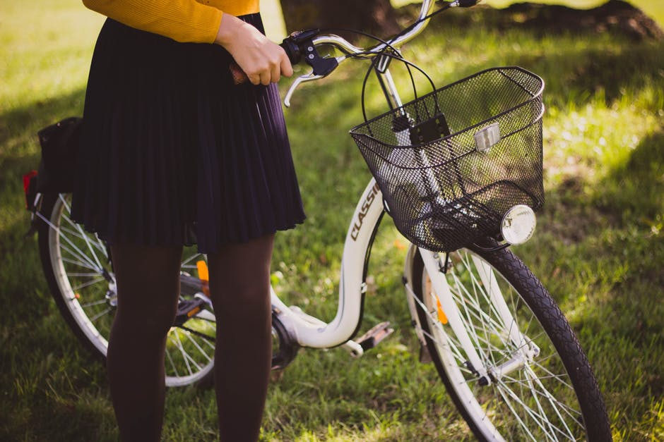 woman wearing a skirt standing with her bike