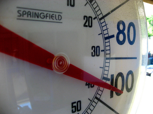 Close up of an outdoor thermometer reading 100 degrees