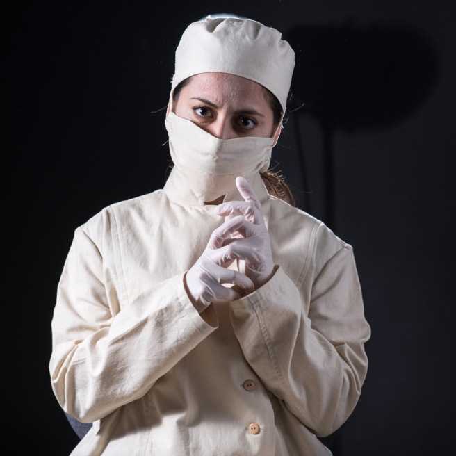 A woman in old fashioned surgeon's gear looks at the camera