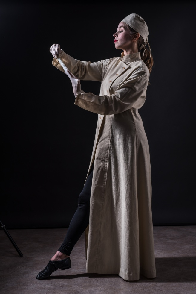 A still from the play Brain Storm, a woman in an old fashioned surgeon's uniform pulls off her gloves