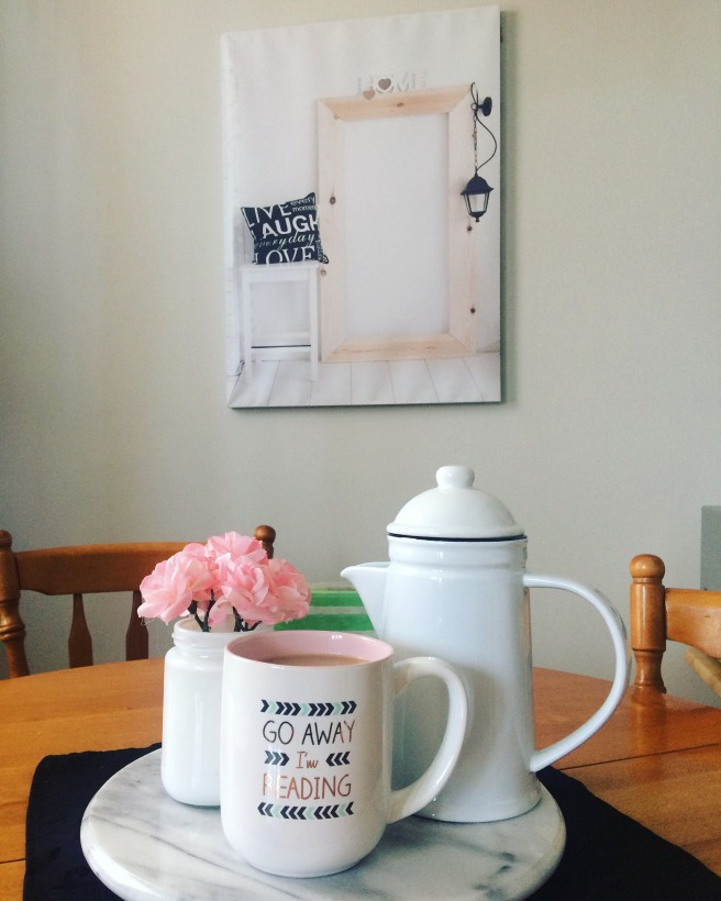 picture of Alyson's home: a picture on the wall of a door with a pillow on a white table that reads 'live, laugh, love' a coffee pot, mug and flowers on a wooden table. Coffee cup reads 'go away I'm reading'