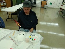 Participant Chris paints his mask for unmasking brain injury