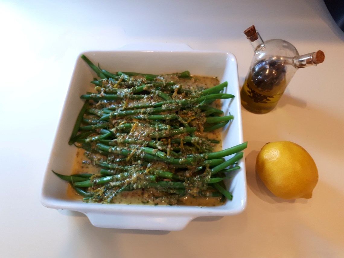 French beans covered in sauce, with vinaiger and lemon on the side