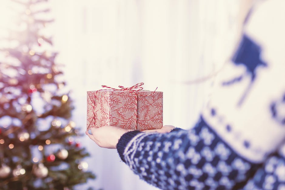 person holding a gift in front of a christmas tree
