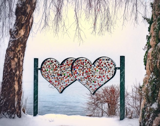 A metal sculpture of two hearts facing a lake in the winter with padlocks locked on the inside grid of both hearts