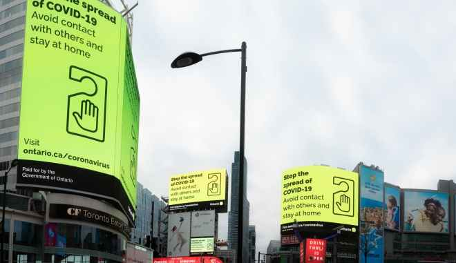 Picture of Dundas Square with large billboards warning of COVID-19